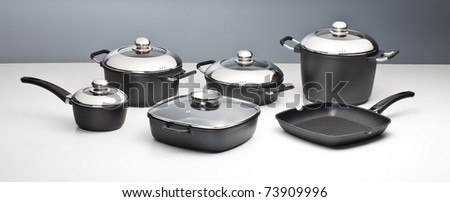 Set of chrome and steel cookware  pots pan - stock photo