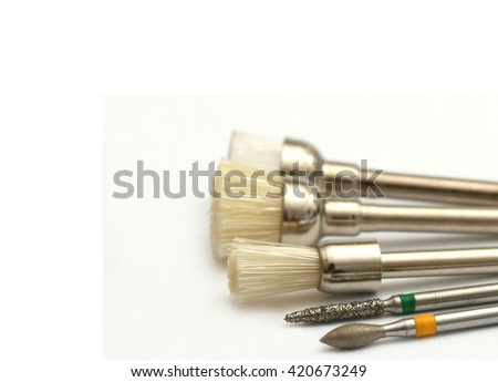 Set of chrome dental drills, viewed from the side on white background and shallow depth of field - stock photo