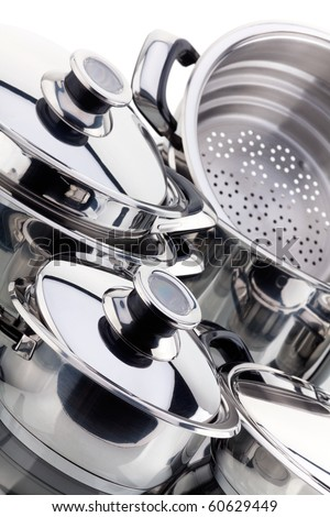 Set of chrome plated aluminum cookware - pots, pans, shot in studio on a white background - stock photo