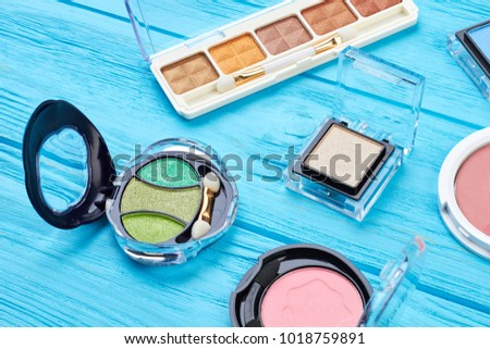 Set of color eyeshadows on blue background. Compact multicolored eyeshadows on wooden table. Woman brand cosmetics.