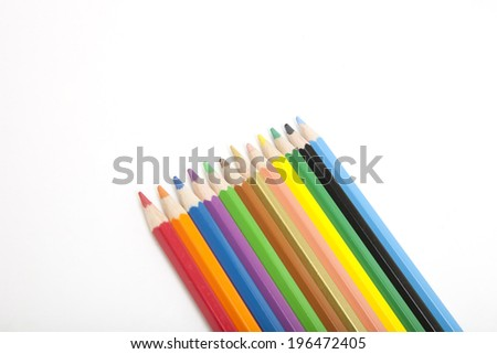Set of colored pencil crayons lying diagonally on a white background with copyspace, conceptual of art, drawing, school and creativity - stock photo
