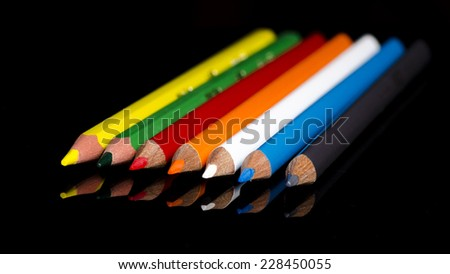 Set of colored pencils with reflection on a black background - stock photo