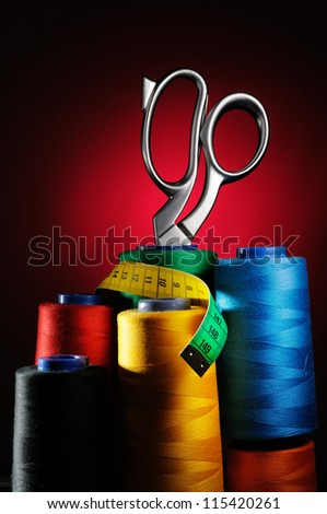 Set of colored threads in the bobbin with scissors and measuring tape - stock photo
