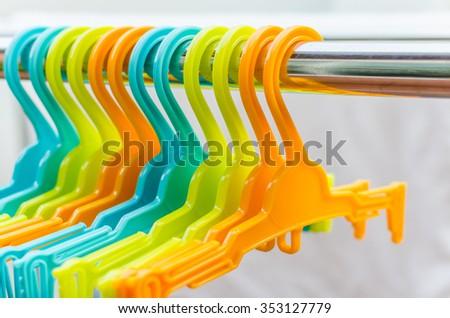 set of colorful coat hanger hanging on rail - stock photo