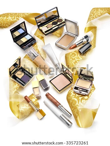 Set of colorful cosmetics against white background. Nail polish, shadows, compact powder and lipsticks. Christmas gift concept - stock photo