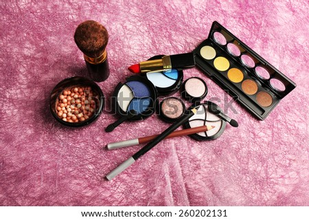 Set of colorful cosmetics on pink textured background - stock photo