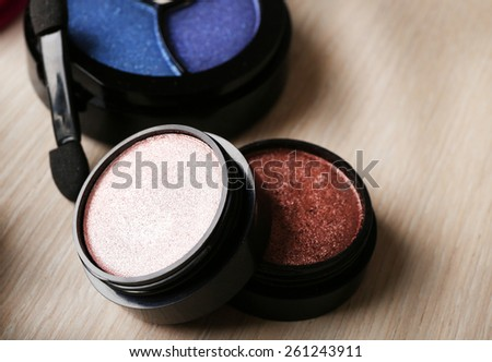 Set of colorful cosmetics on wooden table background
