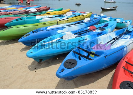 set of colorful kayaks on the beach. - stock photo