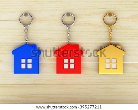 Set of colorful keychains in the form of the houses is hanging on the wooden wall