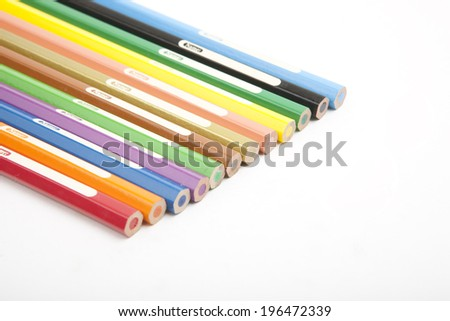 Set of colorful pencil crayons lying diagonally viewed from the back with blank white labels visible on each wooden pencil, conceptual of art, school and creativity, on white with copyspace - stock photo