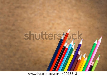 Set of colorful pencils on blurry cork background - stock photo