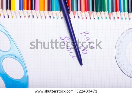 Set of colorful wooden pencils yellow green red pink orange blue and brown lying in row on table with white paper sheet with pen and ruler copyspace, horizontal picture - stock photo