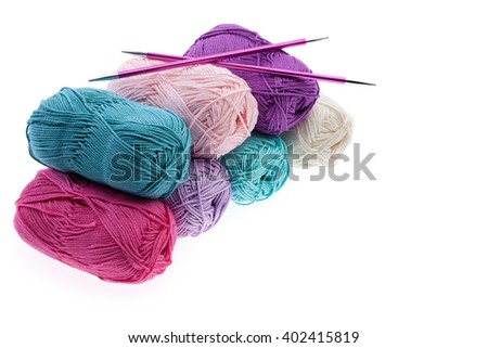 Set of colorful wool yarn wrapped in hanks and a pair of double pointed knitting needles