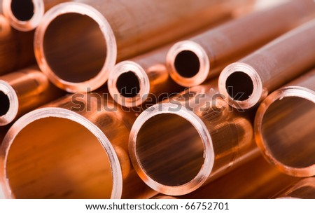 Set of copper pipes of different diameter lying in one heap - stock photo