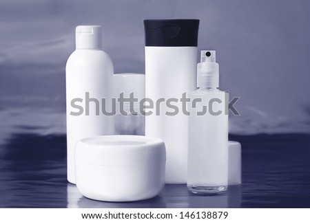 Set of cosmetic containers over blue background