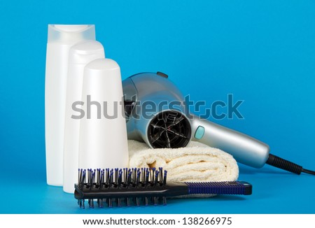 Set of cosmetics, the hair dryer and hairbrush on a towel on a blue background - stock photo