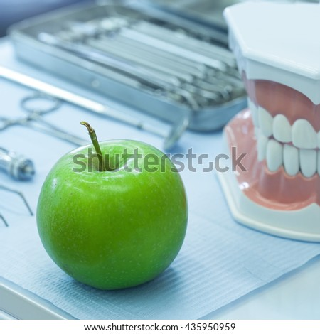 Set of dentistry medical equipment tools and human model jaw with fresh green apple on stomatology table