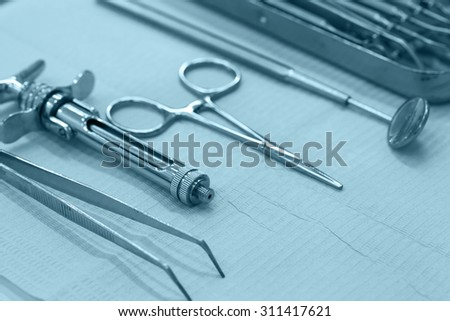 Set of dentistry medical equipment tools on stomatology table. Shallow depth, blue tone image. - stock photo