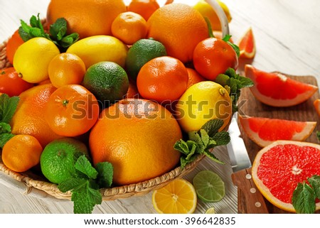 Set of different citrus fruit on light wooden background