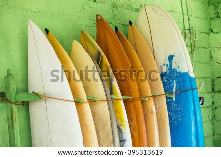Set of different color surf boards in a stack by ocean.Bali,Indonesia. Surf boards on sandy Weligama beach. On Weligama beach surf is available all year around for beginner and advanced. - stock photo