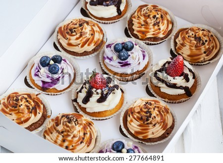 Set of different delicious cupcakes in a paper box - stock photo