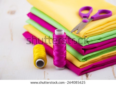 Set of different fabrics, thread spools and tailor scissors - stock photo