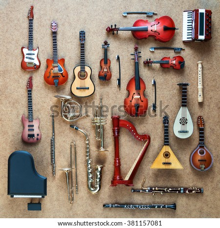 Set of different musical instruments. Golden brass wind and string musical orchestra instruments: saxophone, trumpet, french horn, trombone, violin, cello, contrabass, viola. Grand piano, harp, flute. - stock photo