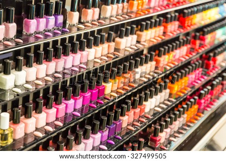 Set of different nail varnishes on shelves in cosmetic store - stock photo