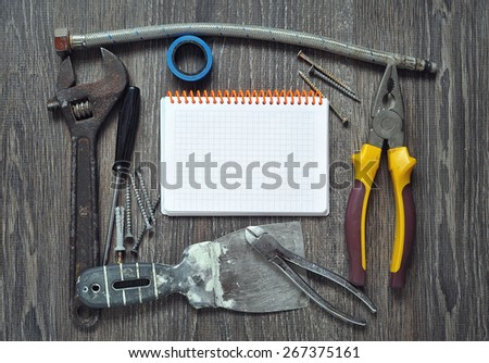 Set of different old Tools  and Notepad on wooden background - stock photo