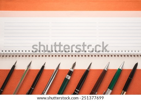 Set of different pens on a notepad