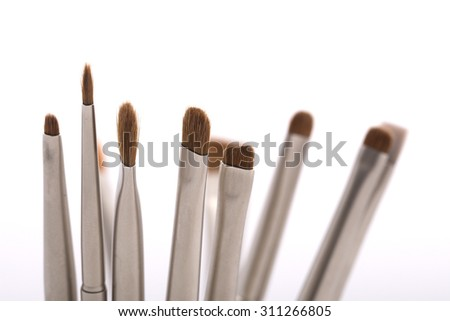 Set of different professional natural soft make-up small brushes for eyeshadow for visagistes grey and brown colors on white background, horizontal picture - stock photo