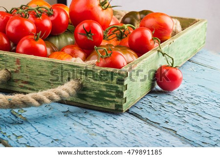 Set of different sorts of ripe tomatoes in the wooden tray, light background