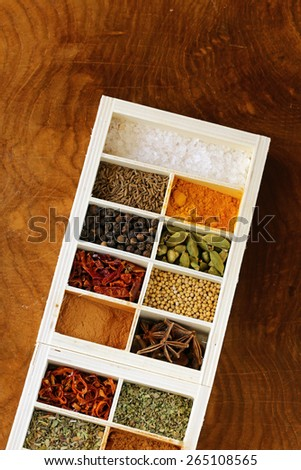 set of different spices (pepper, salt, turmeric, bay leaves, chili, herbs) in a wooden box - stock photo