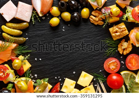 Set of different tasty appetizers, snacks  and ingredients on a black background - stock photo