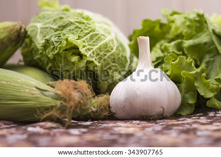 Set of different tasty fresh ripe vegetables ingredients of salad juicy chinese cabbage vibrant lettuce maize cob and spice garlic natural ingredients closeup indoor, horizontal picture - stock photo