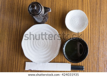 Set of dishes for sushi and rolls. Japanese chopsticks, plate, saucers, rice bowl on wood table - stock photo