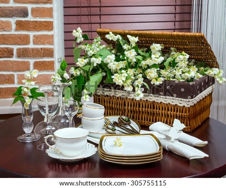 set of dishes, glasses, mug and jasmine flowers in the background wicker basket in the interior. wooden table. close-up