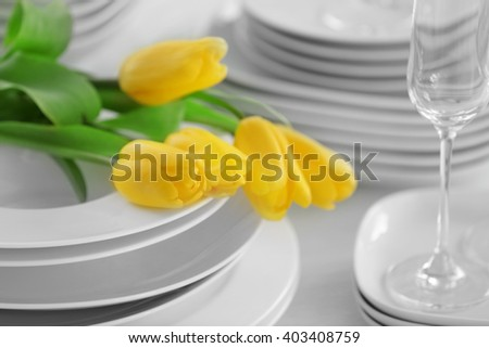 Set of dishes with yellow tulips for dinner party, close up - stock photo