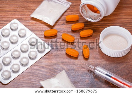 Set of drugs and syringe on wooden table - stock photo