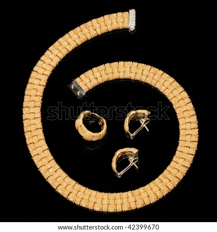 Set of earrings, ring and golden bracelet with diamonds over black background - stock photo