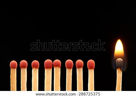 Set of eight red and one burning wooden matches isolated on black background