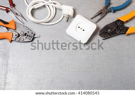 Set of electrical tool on wooden background. Accessories for engineering work, energy concept. - stock photo