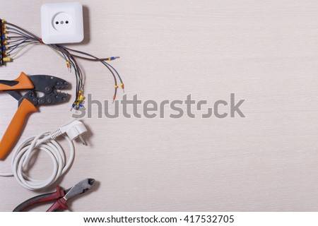 Set of electrical tool on wooden background. Accessories for engineering work, energy concept - stock photo