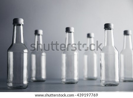 Set of empty cristal unlabeled bottles randomly presented on gray surface, isolated, close focus frontal bottles - stock photo