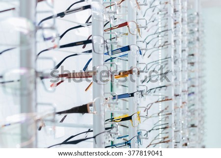 Set of eyeglass frames in the optics store. Close-up showing many eyeglasses in background. - stock photo