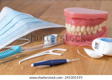 Set of false teeth with dental cleaning tools including a toothbrush, dental floss, disposable face mask and plastic flossing tool in an oral hygiene concept - stock photo