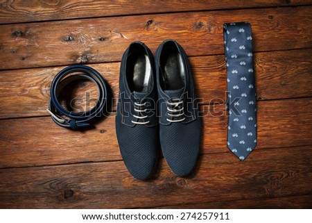 Set of fashionable man's accessories on darkly brown wooden background - stock photo
