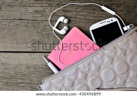 Set of female accessories looks out of the bag. Passport, pen, phone, headphones on a wooden background - stock photo