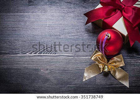 Set of festive bauble bow present box on wooden board. - stock photo