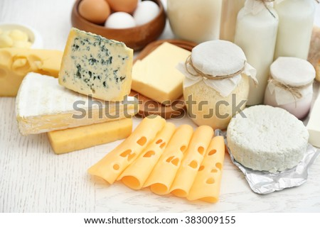 Set of fresh dairy products on white wooden table - stock photo